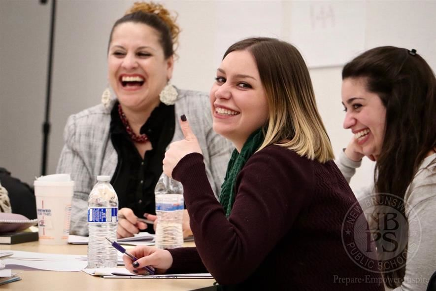A happy teacher smiles during a professional development session.