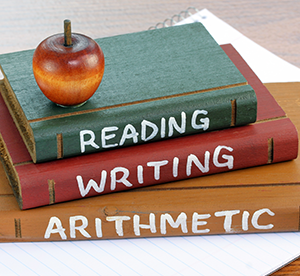 Books on a table saying reading, writing, and arithmetic